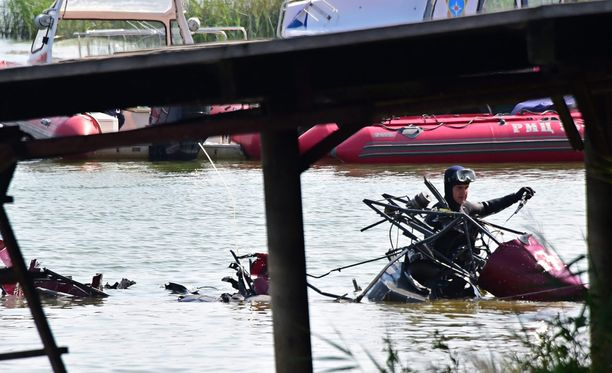 Pelastustyöntekijä kantaa ulos vedestä turmahelikopterin osia Venäjällä Moskovassa tänään.
