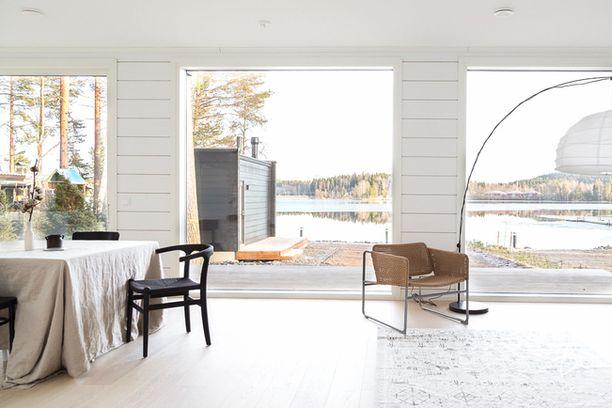 Olohuoneesta avautuu järvimaisema. Siihen yhdistyy myös vaaleasävyinen keittiö, joka ei näy kuvassa.