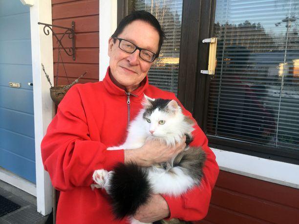 Eläkeläinen Markku Remes ryhtyi ystäväksi ikäihmisille. Sylissä Topi-kissa.