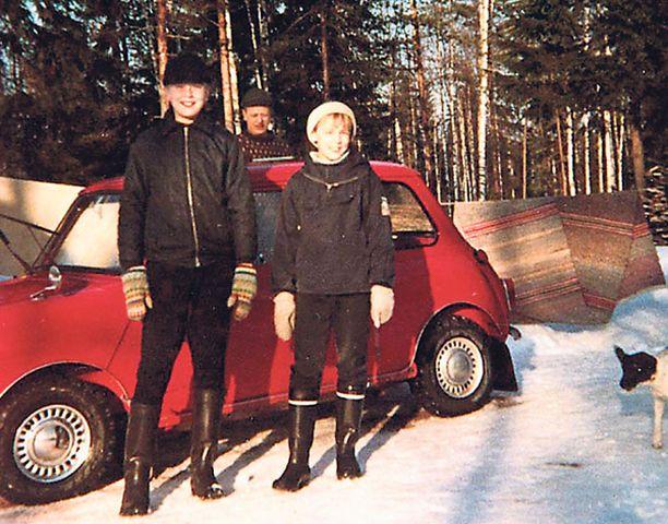 - Meidän ensimmäinen automme Austin Mini ostettiin talvella 1968. Minä ja serkkuni Esa olemme polleina, ja isä kurkistaa takaa. Kuvassa on myös sileäkarvainen kettuterrierimme Evita.