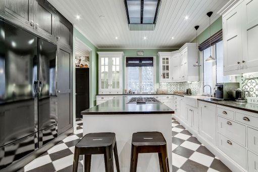 Tämän keittiön näyttäviä yksityiskohtia ovat muun muassa shakkiruutulattia ja erikoiset laatat välitilassa. Säilytys- ja työskentelytilaa on reilusti.
