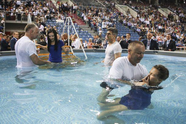 Jehovan todistajat kastavat yhteisön jäseniä upottamalla.