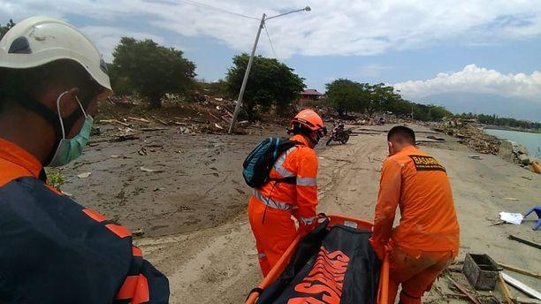 Etsintä- ja pelastusviraston työntekijät kantoivat ruumiita rannalta Palussa lauantaina.