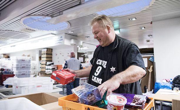 Heikki Hursti on auttanut vähävaraisia jo 12 vuotta. Kuvassa jouluruokapakettien lajittelua Helsingin Kalliossa.