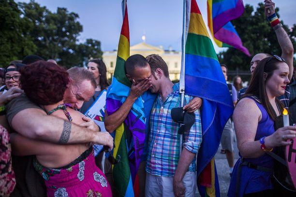 Ihmiset tukivat toisiaan kynttilämielenosoituksessa Valkoisen talon edustalla Orlandon tuhoisan joukkoampumisen jälkeen kesäkuussa 2016.
