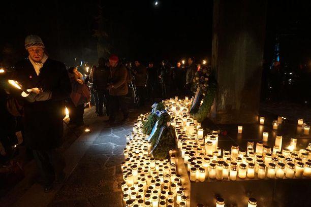 Osallistujat laskivat kynttilöitä sankarihaudoille.