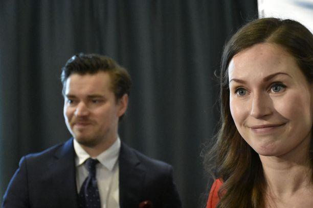 Sanna Marin kertoo, että SDP haluaa muodostaa hallituksen vihreiden ja vasemmistoliiton kanssa. Taustalla myhäilee puoluejohdon viestintävastaava Dimitri Qvintus.