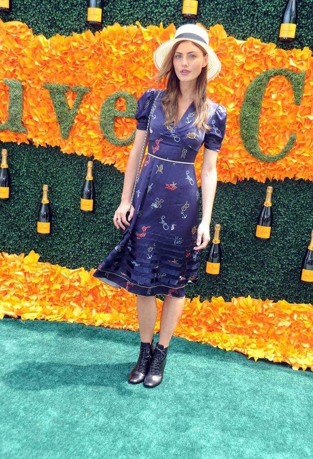 Malli ja näyttelijä Phoebe Tonkin tekee klassisen naisellisesta mekosta nuorekkaan yhdistämällä sen nilkkureihin. Hattu viimeistelee lookin.