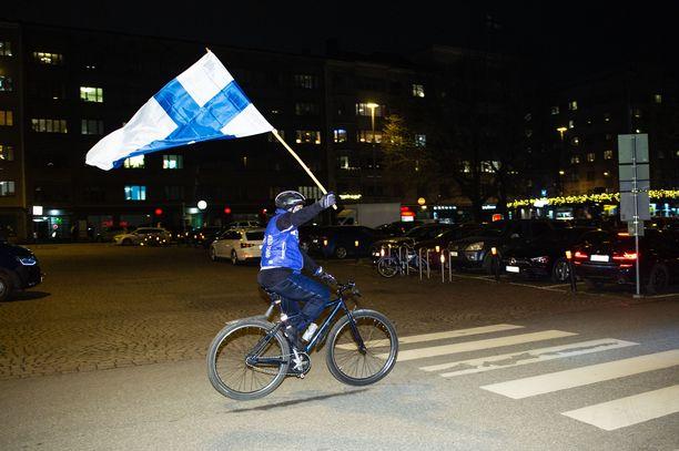 Innokas pyöräilijä polki ympäri Töölöntoria ja heilutti Suomen lippua.