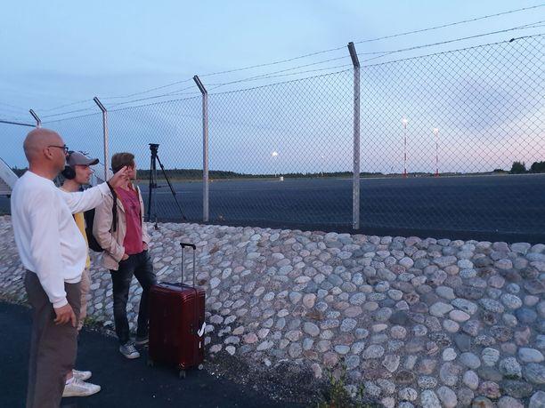 Ihmiset seurasivat pelastusyksiköiden toimintaa lentokentän aidan takana.