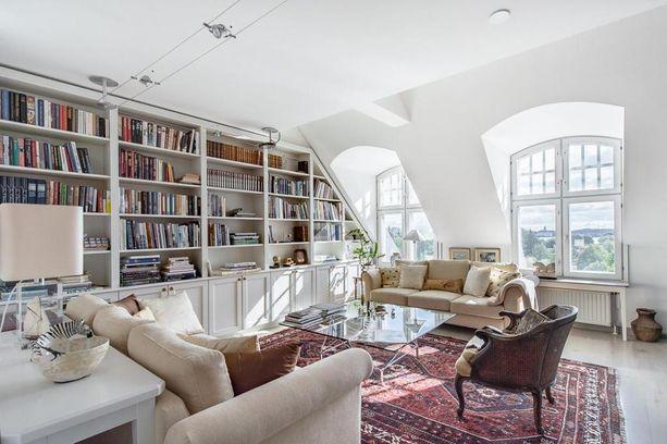 Tässä kodissa kaikki seinätila on käytetty hyödyllisesti viistokattoon räätälöidyllä kirjahyllyllä.