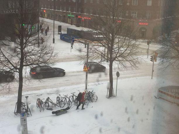 Innokkaimmat ottivat ilon irti runsaasta lumisateesta keskiviikkona. Kuvassa hiihtäjä Helsingin Hakaniemen torilla.