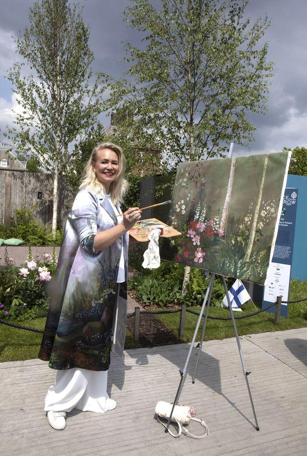 Taidemaalari Johanna Oras maalasi upean kukkaistaulun Taina Suonion puutarhan edessä.