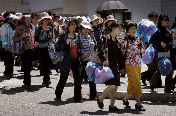 Sunnuntaina Pjongjangissa harjoiteltiin myös puoluekokouksen kunniaksi järjestettävää paraatia varten. Kuvassa harjoituksista palaavia paikallisia.