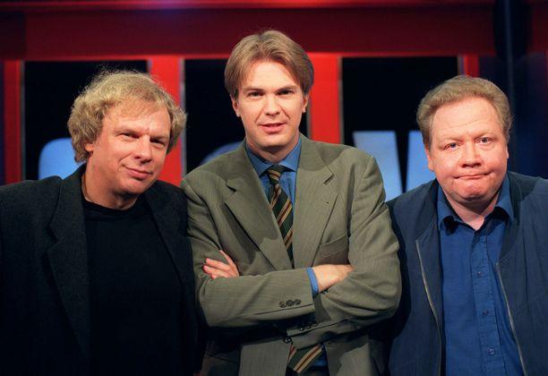 Ohjelman alkuperäinen kokoonpano kuvattuna vuonna 1999: Tommy Tabermann (vas. kapteeni), Peter Nyman (juontaja ja ylituomari) ja Jari Tervo (kapteeni).