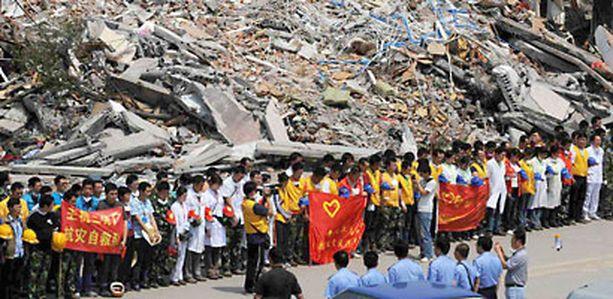 Pelastustyöntekijät viettävät hiljaista hetkeä Hanwangissa, Sichuanin provinssissa.