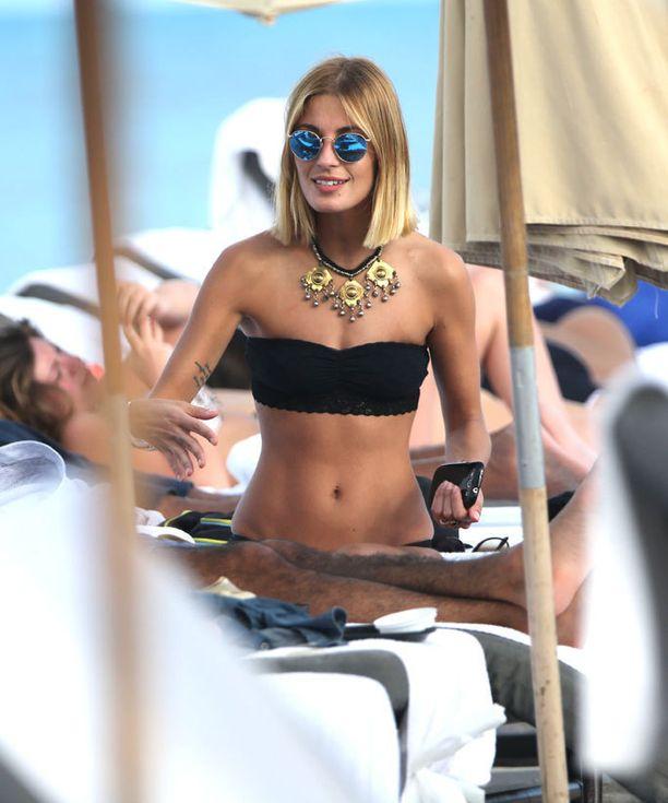 Sveva Alviti puki bikiniensä kanssa massiivisen kaulakorun ja siniset peiliaurinkolasit.