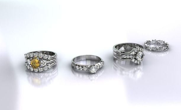 Valkokultaisia timanttisormuksia. Keltainen jalokivi on sitriini.