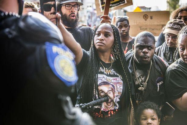 """Desiree' Denard näytti kännykkäänsä poliisille mielenosoituksessa Sacramentossa. Mielenosoittajat huusivat yhdessä """"se on kännykkä""""."""