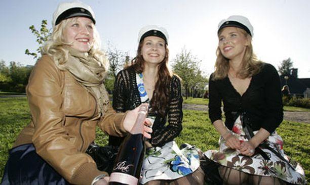 Ylioppilaat Laura Tenhu, Karoliina Oja ja Tiina Räinä odottelivat kavereita ja kaunistivat Ainolan puistoa entisestään.