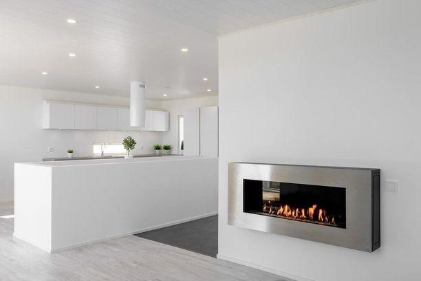 Tässäkin kodissa moderni sisustustakka on kiinnitetty seinään.