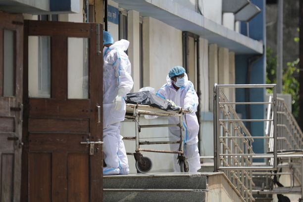 Sairaalatyöntekijät käsittelevät koronaan kuolleen ruumista Kolkatassa itäisessä Intiassa. Maan koronatilanne on levinnyt käsistä.
