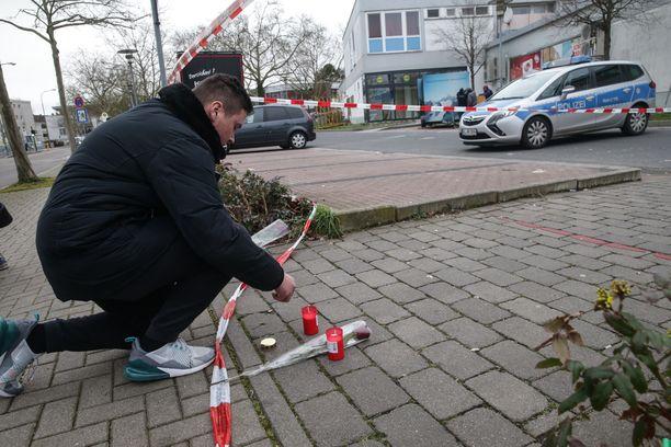 Mies asetti kukkia ja kynttilöitä lähelle yhtä ampumapaikoista.