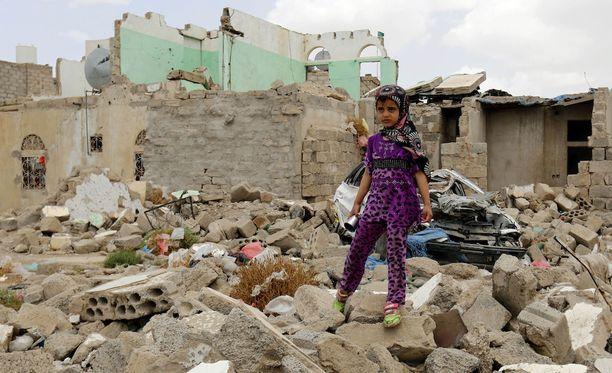 Jemeniläinen lapsi seisoi Saudi-Arabian pommituksissa tuhoutuneiden rakennusten raunioilla Jemenissä maaliskuussa.
