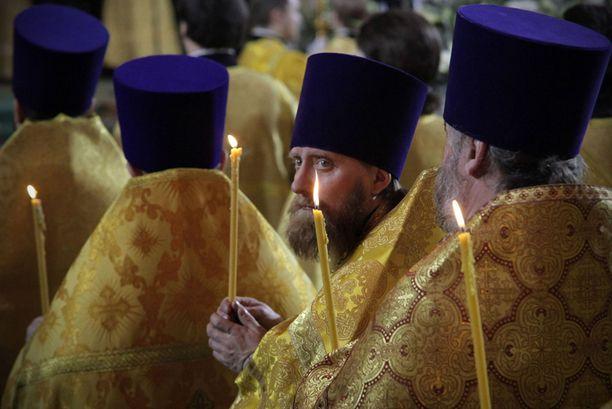 Venäläiset papit pitelivät kynttilöitä messun aikana myöhään torstaina.