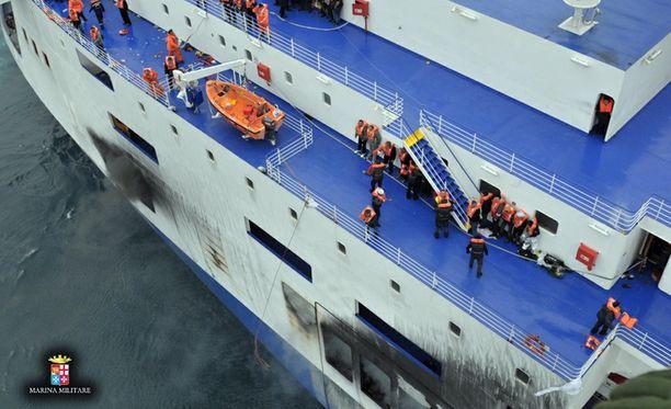 Ilmakuvat näyttävät pelastusta odottavien ihmisten turhauttavan tilanteen palavan aluksen kannella.