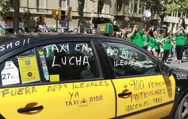 Taksikuskit osoittivat mieltään Uberia vastaan Barcelonassa vuonna 2014. Kirjoituksissa vaadittiin luopumaan laittomista sovelluksista.