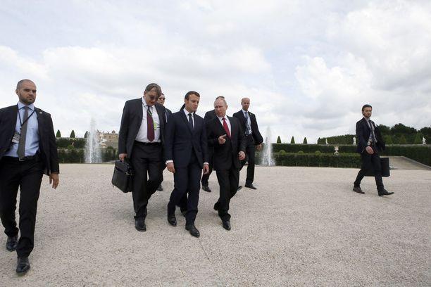 Turvamiesten ulkoisesti tavanomaisilta näyttävät salkut voivat muuntua suojakilviksi tai sarjatuliaseiksi. Kuvassa Venäjän presidentti Vladimir Putin ja Ranskan presidentti Emmanuel Macron turvamiesten ympäröimänä.