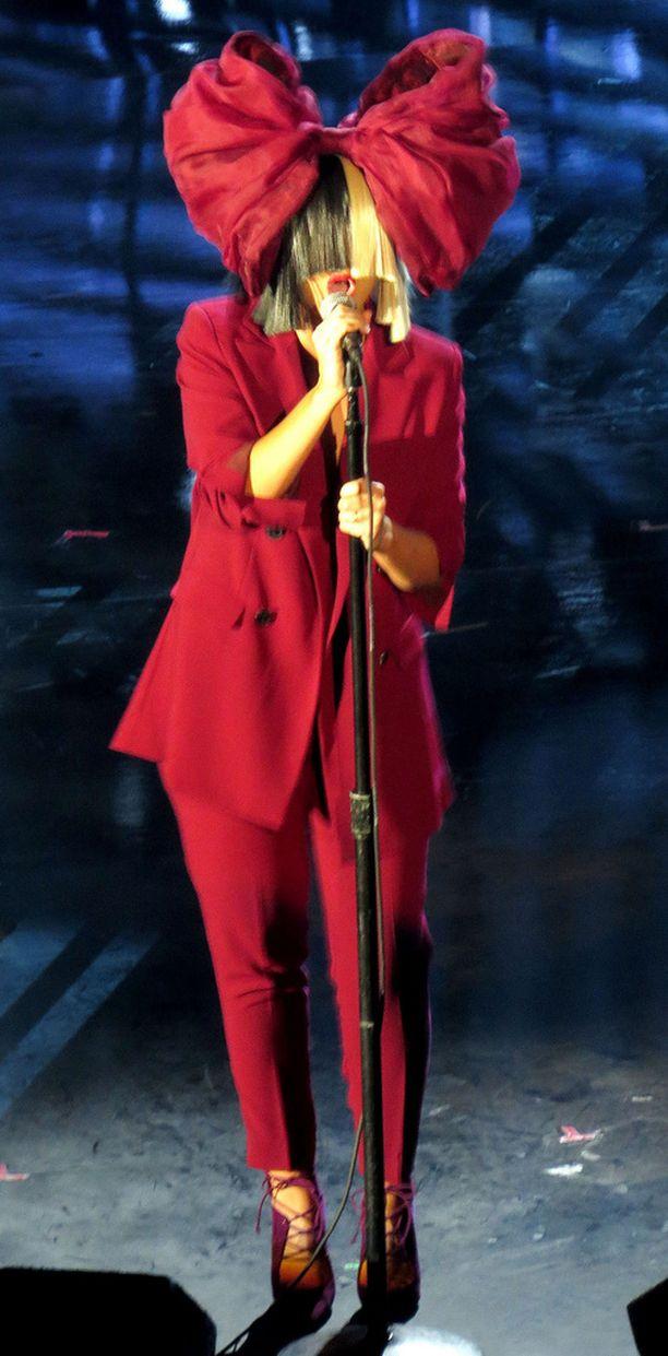 Tyypillisesti Sia esiintyy ison peruukin ja rusetin kera.