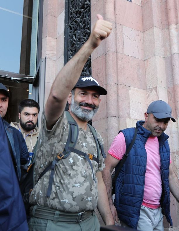 """Nikol Pashinianin tavaramerkit mielenosoituksissa olivat maastokuvioitu t-paita ja reppu, joka sisältää hänen itsensä mukaan """"kaiken tarvittavan"""", kuten kannettavan tietokoneen ja suklaata."""