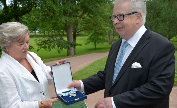 Rouva Tuula Kummola ojensi ansioristin aviomiehelleen valokuvaajien pyynnöstä.