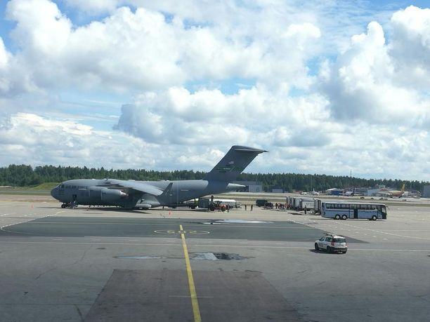 Kuvassa näkyy, kuinka kuorma-autot odottavat lentokoneesta purettavia kontteja lentoaseman liikennealueella.