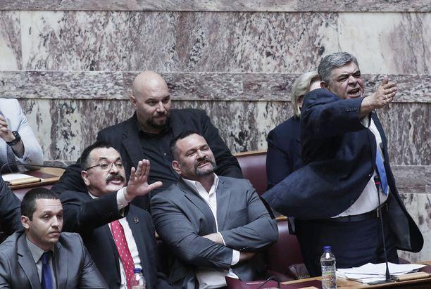 Kultaisen aamunkoiton johtaja Nikos Michaloliakos (oik.) oli aggressiivisella tuulella parlamentissa viime viikolla.