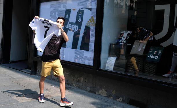 Juventuksen kannattaja juoksi ulos fanikaupasta tuoreen Ronaldo-paidan kanssa Torinossa keskiviikkona.