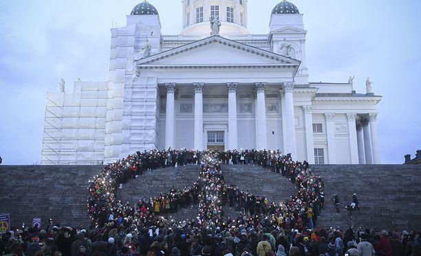 Save Syria? -marssilla 2016 suomalaiset muodostivat rauhanmerkin Helsingin Tuomiokirkon portaille.