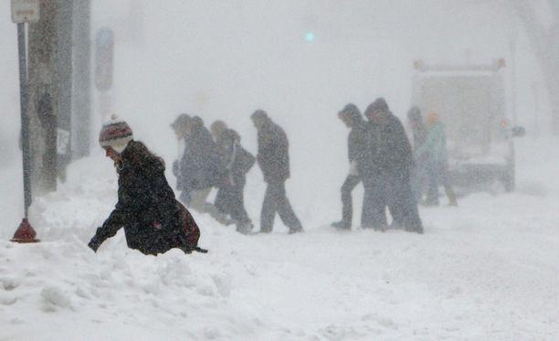 Jalankulkijat taistelivat lumimyrskyä vastaan.