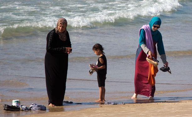 Burkinipukuisia naisia rannalla Israelin Tel Avivissa perjantaina. Kuvituskuva.