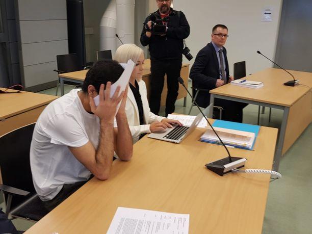 Mies peitti kasvonsa oikeusistunnon aluksi.