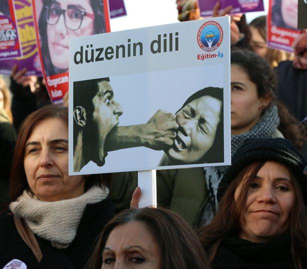 """Mielenosoittajat protestoivat Ankarassa naisiin kohdistuvaa väkivaltaa vastaan. Kyltissä lukee """"järjestelmän kieli""""."""