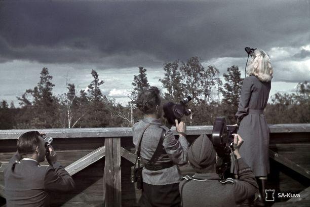 Ilmavalvontalotta Ellen Kiuru keskellä kuvauksia Lahdenpohjan ilmavalvontatornissa heinäkuussa 1942. Suomalaisen tiedotuskomppanian kuvaajan lisäksi mukana projektissa olivat saksalaiset pikakiväärimiehet.