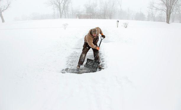 Mies lapioi lunta ajotieltä kotipihassaan Kentuckyssa.