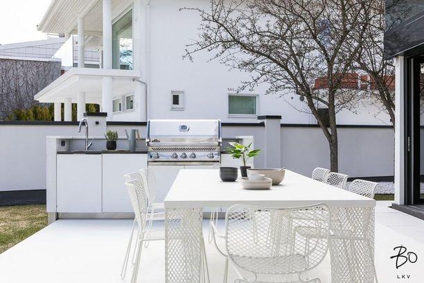 Terassin yhteydessä oleva kesäkeittiö jatkaa talon modernia linjaa siinä määrin, että ensisilmäyksellä voisi kuvitella talon varsinaisen keittiön muuttaneen kokonaan ulkotiloihin.