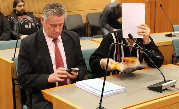 Kuvissa on äänekoskelaisen Toni Rämäsen surmasta syytetty ja puolustusasianaja Henry Saleva. Syytetty piilottelee Alibi-lehden takana.