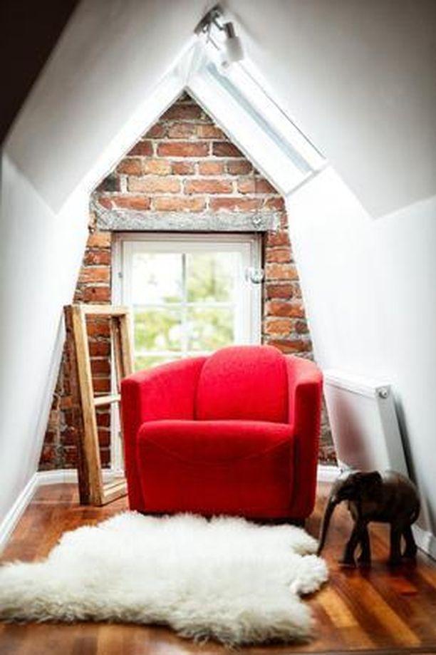 Tiiliseinä, punainen nojatuoli ja talja lattialla tekevät Helsingin Kampissa sijaitsevan ullakkoasunnon kattolyhdystä tunnelmallisen lukunurkkauksen.