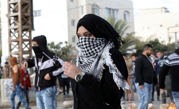 Mielenosoituksiin osallistunut palestiinalaisnainen lähestyy israelilaissotilaita yhteenotossa Huwwaran tarkistuspisteellä, lähellä Länsirannalla sijaitsevaa Nablusia.