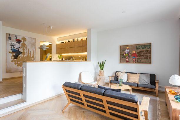 Näin valkoinen kalsea vaikutelma vältetään puisten huonekalujen ja pastellisävyisten tekstiilien avulla! Kiinnostava arkkitehtuurinen yksityiskohta on korokkeella sijaitseva keittiö, johon johtaa pienet portaat.